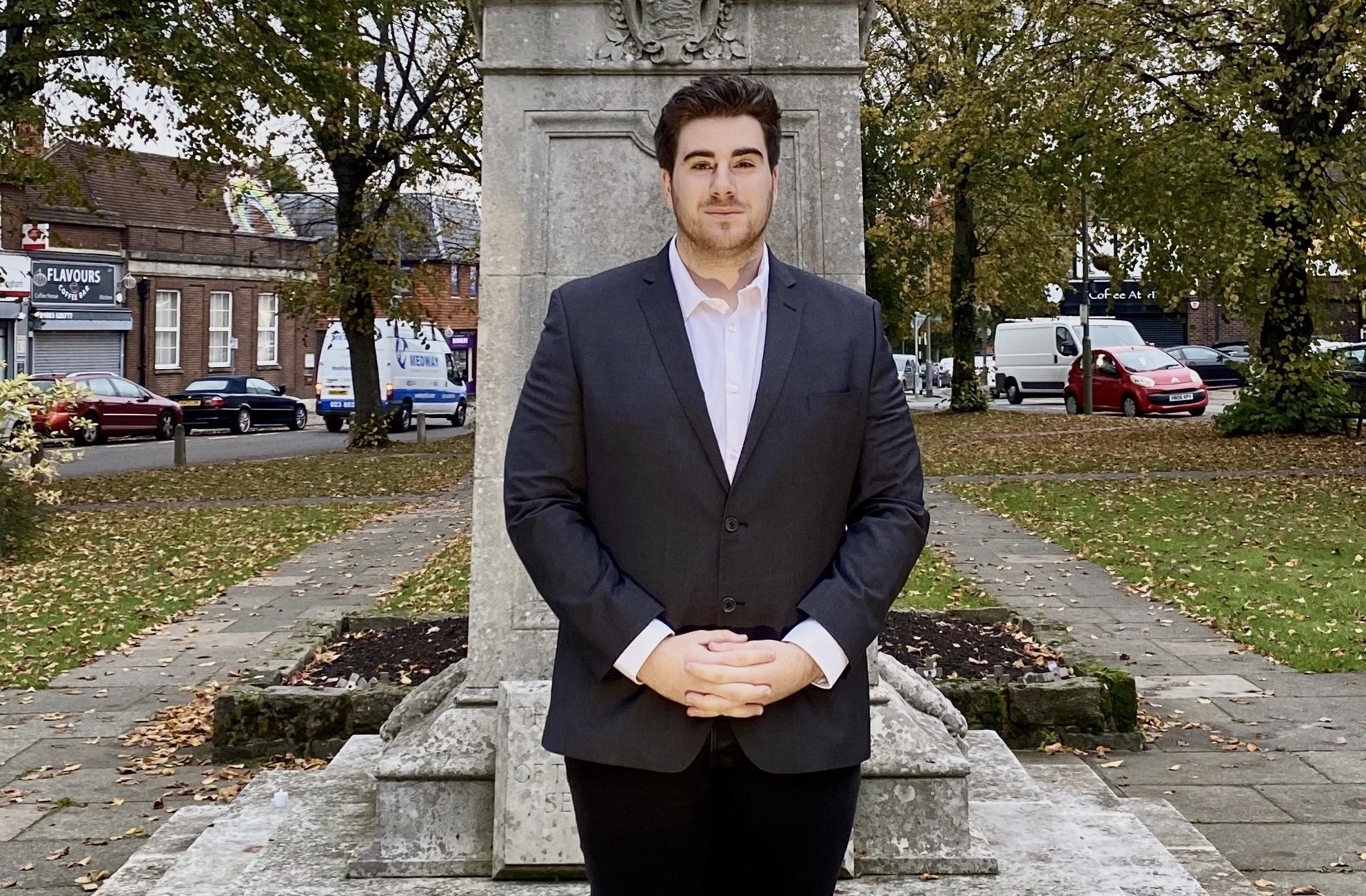 Josh Newman stood in front of statue